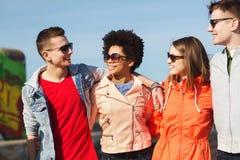 Amis adolescents heureux aux nuances parlant sur la rue Images stock