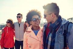 Amis adolescents heureux aux nuances parlant sur la rue Photo stock