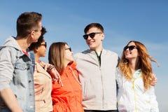 Amis adolescents heureux aux nuances parlant sur la rue Photographie stock