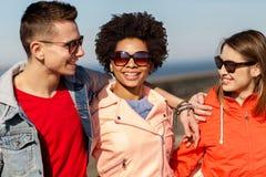 Amis adolescents heureux aux nuances parlant sur la rue Photos stock
