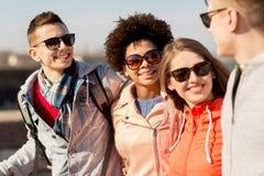 Amis adolescents heureux aux nuances parlant sur la rue Images libres de droits