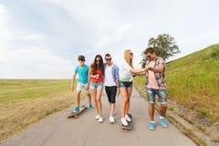 Amis adolescents heureux avec des longboards dehors Photographie stock
