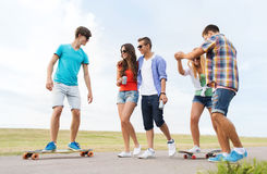 Amis adolescents heureux avec des longboards dehors Images stock