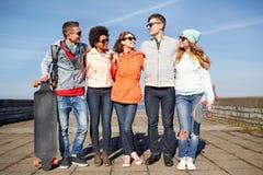 Amis adolescents heureux avec des longboards sur la rue Photographie stock