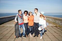 Amis adolescents heureux avec des longboards sur la rue Image libre de droits