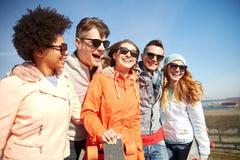 Amis adolescents heureux avec des longboards sur la rue Photo stock