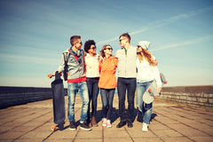 Amis adolescents heureux avec des longboards sur la rue Images stock