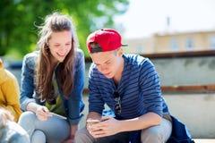 Amis adolescents heureux avec des smartphones dehors Photographie stock