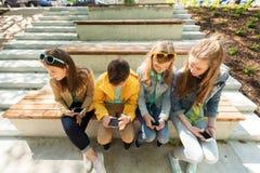 Amis adolescents heureux avec des smartphones dehors Photo stock