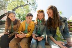 Amis adolescents heureux avec des smartphones dehors Photo libre de droits
