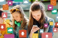 Amis adolescents heureux avec des smartphones dehors Images stock