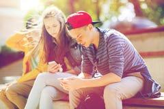 Amis adolescents heureux avec des smartphones dehors Image libre de droits