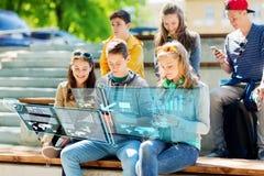 Amis adolescents heureux avec des smartphones dehors Image stock
