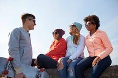Amis adolescents heureux avec la planche à roulettes sur la rue Image libre de droits