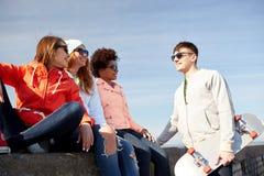 Amis adolescents heureux avec le longboard sur la rue Photo libre de droits