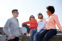 Amis adolescents heureux avec le longboard sur la rue Photographie stock libre de droits