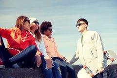 Amis adolescents heureux avec le longboard sur la rue Image libre de droits