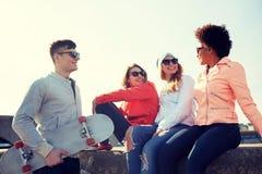 Amis adolescents heureux avec le longboard sur la rue Photographie stock