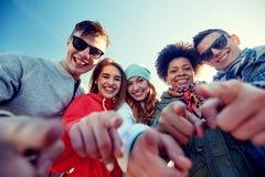 Amis adolescents heureux dirigeant des doigts sur la rue Photos stock