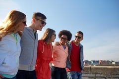 Amis adolescents heureux marchant le long de la rue de ville Image stock