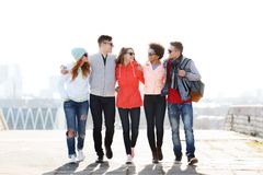 Amis adolescents heureux marchant le long de la rue de ville Image libre de droits