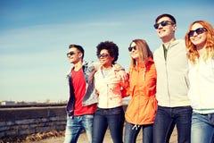 Amis adolescents heureux marchant le long de la rue de ville Photographie stock libre de droits