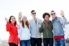 Amis adolescents heureux ondulant des mains sur la rue de ville Photo stock