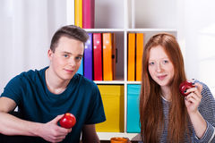 Amis adolescents mangeant la pomme Photos stock