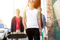 Amis adolescents marchant à la rue Photos stock