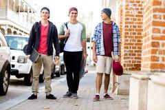 Amis adolescents marchant à la rue Photographie stock libre de droits
