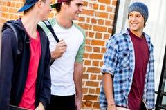 Amis adolescents marchant à la rue Images libres de droits
