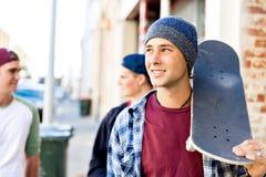 Amis adolescents marchant à la rue avec des planches à roulettes Photographie stock libre de droits