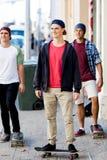 Amis adolescents marchant à la rue avec des planches à roulettes Photo stock
