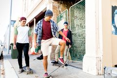 Amis adolescents marchant à la rue avec des planches à roulettes Photographie stock