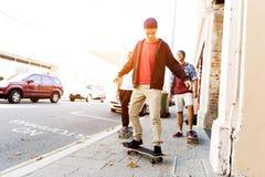Amis adolescents marchant à la rue avec des planches à roulettes Image stock