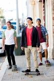 Amis adolescents marchant à la rue avec des planches à roulettes Photos stock