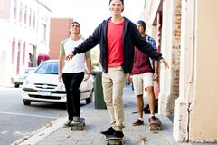 Amis adolescents marchant à la rue avec des planches à roulettes Photo libre de droits