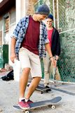 Amis adolescents marchant à la rue avec des planches à roulettes Images stock