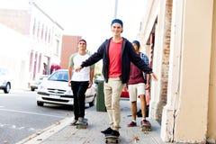 Amis adolescents marchant à la rue avec des planches à roulettes Photos libres de droits