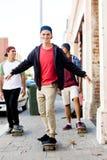 Amis adolescents marchant à la rue avec des planches à roulettes Image libre de droits