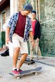 Amis adolescents marchant à la rue avec des planches à roulettes Images libres de droits