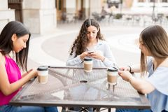 Amis adolescents mignons à l'aide des smartphones au café Images libres de droits