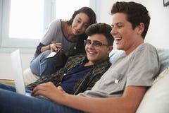 Amis adolescents observant quelque chose drôle sur l'ordinateur portable Photo libre de droits