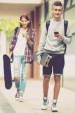 Amis adolescents portant des planches à roulettes dans la ville Photo libre de droits
