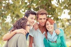 Amis adolescents prenant des autoportraits Images stock