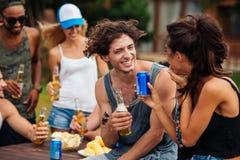 Amis adolescents s'asseyant à la table et ayant l'amusement dehors Photo libre de droits