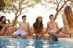 Amis adolescents s'asseyant au bord d'une piscine Photos stock