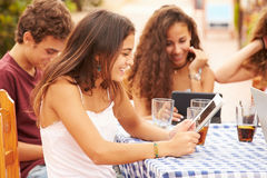 Amis adolescents s'asseyant au ½ de ¿ de Cafï utilisant des dispositifs de Digital Image stock