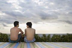 Amis adolescents s'asseyant sur l'océan de négligence de plate-forme Photographie stock