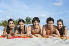 Amis adolescents se situant dans la rangée sur des serviettes de plage image stock